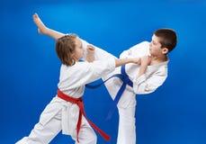 In karategi doen twee atleten blokken en schoppen van karate stock afbeelding