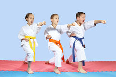 In karategi three athletes are hitting karate kick arm Royalty Free Stock Images