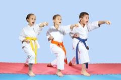 In karategi three athletes are hitting karate kick arm. In karategi athletes are hitting karate kick arm Royalty Free Stock Images