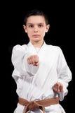 Karatejongen in het witte kimono vechten geïsoleerd op zwarte achtergrond royalty-vrije stock afbeeldingen