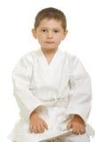 Karatejunge, der auf Knien sitzt stockfoto