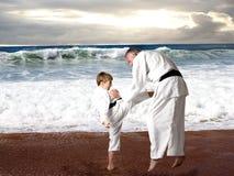 Karatejunge, der sein Sensei tritt Stockbild