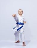 Karateka男孩打在轻的背景的拳打胳膊 免版税库存图片