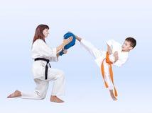 Karateka bate um pontapé na almofada dobro do pontapé fotografia de stock