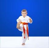 Karateka hits a kick on a blue background Royalty Free Stock Photos