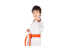 Karateka with a orange belt. The boy stands in white kimono of the karate with a orange belt Royalty Free Stock Images