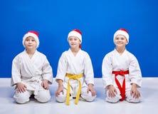 Karateka tre i lock av Santa Claus sammanträde i en karate poserar Royaltyfria Foton