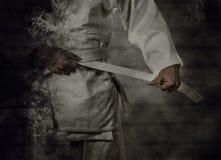 Karateka tying the white belt (obi) with grunge background Royalty Free Stock Photo
