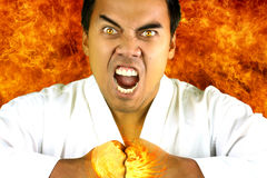 Karateka who expresses anger. Young karateka who expresses anger on a background with flames royalty free stock photo