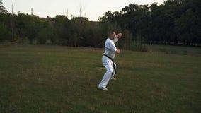 Karatekmannen i den vita kimonot utför katakarateaktiviteter på fältet i morgonen i staden parkerar stock video
