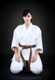 Karatekvinnan i grundläggande karate poserar Arkivbilder