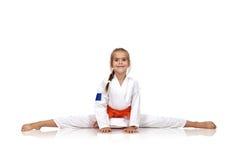 Karatemädchen, das auf Spalten sitzt stockbild