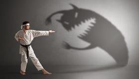 Karatemanstridighet med en stor läskig skugga fotografering för bildbyråer