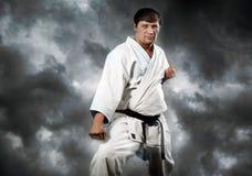 Karatemeister im Kimono auf stürmischem Himmel stockfoto
