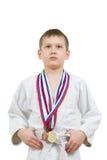 Karatepojke i den vita kimonot med att slåss för medaljer Royaltyfria Bilder