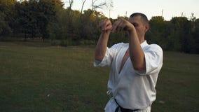 Karatepraktiker som en man i den vita kimonot gör idrottshallen qigong, utför kata i morgonen på gläntan i stad parkerar lager videofilmer