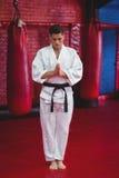 Karatespeler de status in gebed stelt royalty-vrije stock afbeelding