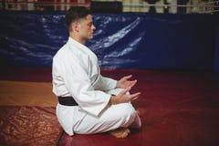 Karatespeler die yoga doen royalty-vrije stock afbeelding
