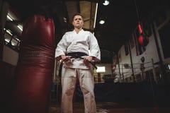 Karatespeler die zijn riem binden stock foto's