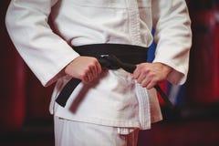 Karatespeler in zwart band royalty-vrije stock afbeeldingen