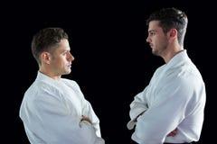 Karatespelers die zich met gekruiste wapens bevinden stock afbeeldingen