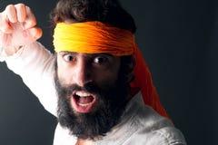Karatestående med det ilskna uttryckt som poserar mot grå bakgrund arkivfoton