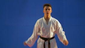 Karateungekämpe som övar stansa och sparkande tekniker under utbildning på dojoen stock video