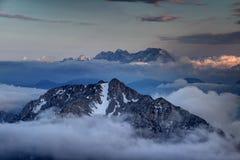 Karavanke范围峰顶和卡姆尼克萨维尼亚河阿尔卑斯在云彩上上升 库存图片