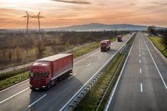 Karawana Czerwona ciężarówka przewozi samochodem na autostradzie zdjęcia royalty free