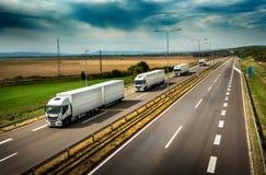 Karawana lub konwój Biała ciężarówka przewozimy samochodem na autostradzie zdjęcie stock