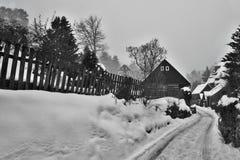 Karba, Machuv kraj,捷克共和国- 2017年2月04日:木村庄和岩石在背景在多雪的冬天 图库摄影