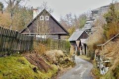 Karba, kraj de Machuv, República Checa - 14 de abril de 2013: cabañas y roca de madera en fondo en primavera Foto de archivo libre de regalías