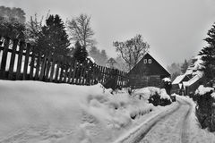 Karba, Machuv kraj, Czech republic - February 04, 2017: wooden cottages and rock on background in snowy winter Stock Photography