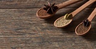 Kardemom, kruidnagels, steranijsplant Maalde kruiden in houten lepels Dif royalty-vrije stock foto