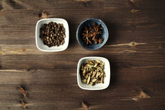 Kardemumman anis, kryddpeppar, den blandade kryddan i keramik bowlar på trä fotografering för bildbyråer