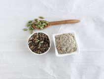 Kardemummapulver och frö i bunkar och kardemummafröskidor på en träsked royaltyfri fotografi