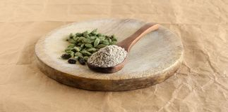 Kardemummapulver på en träsked och kardemummafröskidor och frö arkivfoton