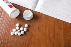 Kardiograma wydruk i białe pigułki rozlewa z butelki zdjęcie stock