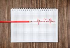 Kardiogramm, einen roten Bleistift auf weißem Notizbuch zeichnend Lizenzfreie Stockfotografie