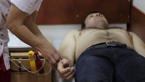Kardiologdoktor som förbereder patienten för borttagning av kardiogrammet stock video