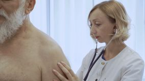 Kardiologen lyssnar tillbaka av hög man med stetoskopet stock video