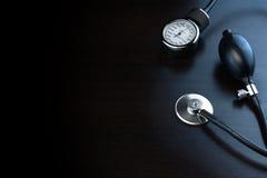 Kardiologie-medizinische Ausrüstung auf schwarzer hölzerner Hintergrund-herein Rückseite stockfotografie