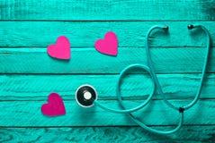 Kardiologieausrüstung Hören Sie zu Ihrem Inneren Das Konzept von Sorgfalt für das Herz Stethoskop, Herzen auf einer Türkisholzobe Stockfotos