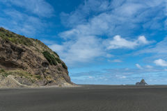 Karekare Beach with the Watchman Rock in distance. Auckland, New Zealand - March 2, 2017: Wide shot of black sand Karakare Beach under blue cloudy sky with, Te Royalty Free Stock Images