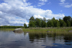 Karelian lake with huge boulders. The beautiful picture of Karelian forest at the edge of a lake, and some huge boulder in this lake royalty free stock photography
