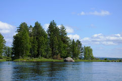 Karelian lake with huge boulders. The beautiful picture of Karelian forest at the edge of a lake, and some huge boulder in this lake stock photo