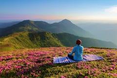 Karemat variopinto La ragazza di yoga nella posa del loto Il prato inglese con i fiori del rododendro Alte montagne meditazione d Immagine Stock