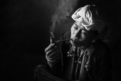 Karen hill tribe is smoking tobacco pipe with traditional clothes Stock Images