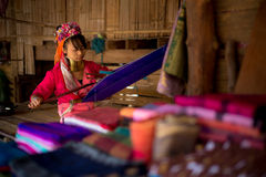 Karen long necked tribe woman weaves on a loom in hills near Chiang Mai, Thailand. CHIANG MAI, THAILAND - NOV 28, 2013: Karen long necked tribe woman weaves on a stock image