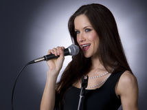 Kareoke Girl Sings Song Performer Microphone. A Beautiful woman sings into the microphone Stock Image